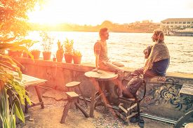 stock photo of experiments  - Couple of best friends travelers talking at sunset  - JPG
