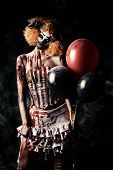Постер, плакат: Evil redhead clown stained in blood holding balloons Female zombie clown Halloween Horror