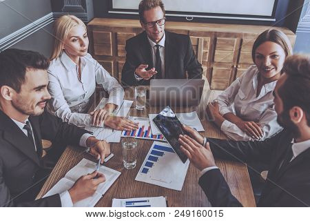 poster of Group Of Business People Using Digital Tablet Together. Business People Meeting Communication Discus