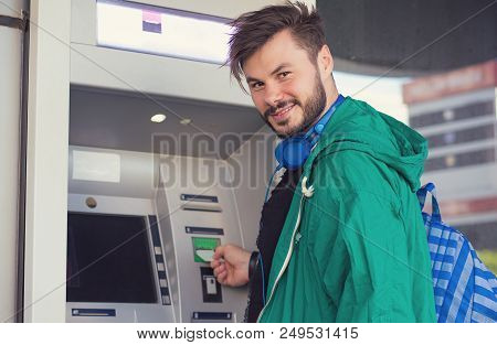 poster of Young Hipster Guy In Headphones Smiling At Camera While Inserting Credit Card In Atm Machine Getting