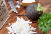 stock photo of grated radish  - Black radish rub on a small grater for salad preparation