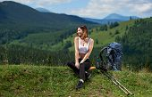 Young Sporty Woman Backpacker With Backpack And Trekking Poles Sitting With Closed Eyes, Relaxing Af poster