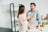 Affectionate Couple Clinking With Wineglasses In Kitchen poster