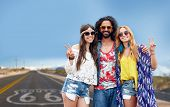 nature, summer, youth culture, gesture and people concept - smiling young hippie friends in sunglass poster