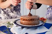 Home Confectionery. Two Girls Making A Cake On The Kitchen.women Cooking A Cake With Chocolate Cream poster