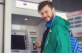 Young Hipster Guy In Headphones Smiling At Camera While Inserting Credit Card In Atm Machine Getting poster