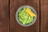 An Overhead Photo Of Guacamole Sauce In A Molcajete, Traditional Mexican Mortar, On A Dark Rustic Ba poster