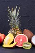 Assorted Tropical Fruits On Black Textured Background. Assortment Of Whole And Sliced Exotic Fruits. poster