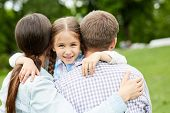 Hapy child embracing her mother and father and looking at camera during chill in park poster
