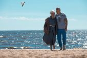 Mature affectionate couple walking down sandy beach with sea behind and blue sky above poster