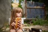 Portrait Of Poor Hungry Homeless Girl Eating A Piece Of Bread In The Dirty Alley, Selective Focus. P poster