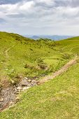 French Pyrenees Mountains Steep May Grassland Hills With A Mountain Rill, Dramatic Overcast Sky, Pyr poster