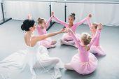 Happy Little Ballerinas And Ballet Teacher Sitting And Holding Hands In Ballet School poster
