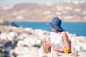 Beautiful Elegant Girl Having Breakfast At Outdoor Cafe With Amazing View On Mykonos Town. Woman Dri poster