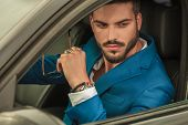 handsome man in blue suit driving his car looks on window while holding sunglasses poster
