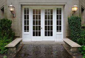 stock photo of front door  - Elegant stone walkway bordered by stone benches leading to a double glass paned front door with two large front lanterns - JPG