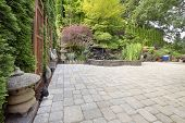 image of garden sculpture  - Backyard Garden Asian Inspired Paver Patio with Pagoda Pond Bronze and Stone Sculptures - JPG