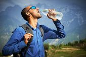 Thirsty traveller in Himalayas mountains drinking pure fresh water from bottle