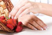 stock photo of french manicure  - Beautiful hands with French manicure and fresh strawberry - JPG
