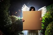 stock photo of garden eden  - Angel woman with white wings holding blank cardboard message board poster in night garden - JPG