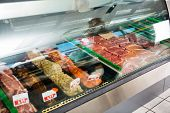 Variety of meat displayed in glass cabinet at butcher's shop