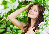 stock photo of nearly nude  - Portrait of young woman touches her face standing near the blossomed tree in the park - JPG