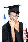 stock photo of school-leaver  - Graduating student in glasses with the diploma adjusts the spectacles - JPG
