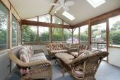 stock photo of screen-porch  - Porch in suburban home with wicker furniture - JPG