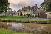 stock photo of slaughter  - Pretty Cotswold cottages at the popular tourist destination of Lower Slaughter near Bourton on the Water - JPG