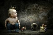Baby boy around their toys looking at the image on the grunge wall
