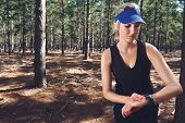 stock photo of gps  - Woman runner checking pace on gps sports watch in forest - JPG