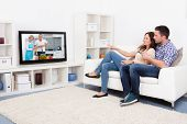 picture of watching movie  - Young Couple Sitting On Couch Watching Cookery Show - JPG