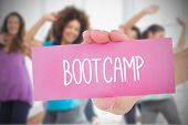 stock photo of single woman  - Woman holding pink card saying bootcamp against fitness class in gym - JPG