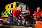 stock photo of stretcher  - Paramedical team assisting injured man motorbike driver at night - JPG