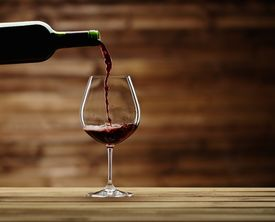 stock photo of flavor  - Pouring red wine into the glass against wooden background - JPG