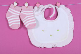 stock photo of girlie  - Baby girl nursery cute pink and white stripe socks and bib hanging from pegs on a line against a pink background for baby shower or newborn girl greeting card - JPG