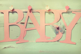 stock photo of girlie  - Retro Filter pink baby girl nursery BABY letters bunting hanging from pegs on a line against a vintage aqua blue shabby chic background for baby shower or newborn girl greeting card - JPG