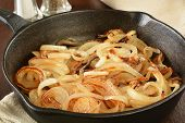 stock photo of sauteed  - Sauteed onions in a cast iron skillet with condiments in the background - JPG