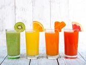 pic of fruit-juice  - Fruit and vegetable juice in glasses and pieces of fresh fruits on wooden table on wooden wall background - JPG
