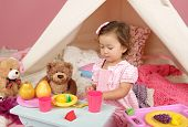 picture of teepee tent  - Happy toddler girl engaged in pretend play tea party indoors at home with a teepee tent - JPG