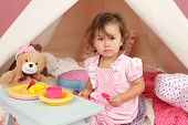 stock photo of teepee tent  - Happy toddler girl engaged in pretend play tea party indoors at home with a teepee tent - JPG
