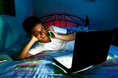picture of web surfing  - Photo of a Young Teen in front of a laptop computer and on a bed and using a cellphone or smartphone - JPG