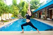 stock photo of virabhadrasana  - Beautiful Asian Girl practicing warrior virabhadrasana I yoga pose by the pool - JPG