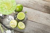 stock photo of cocktail  - Classic margarita cocktail with salty rim on wooden table with limes and drink utensils - JPG