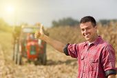 stock photo of tractor  - Young satisfied farmer showing thumbs up tractor on field in background - JPG