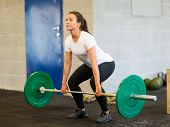 image of barbell  - Full length of young woman lifting barbell in gym - JPG