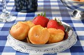 stock photo of cream puff  - A plate of cream puffs and strawberries on a picnic table - JPG
