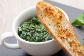 picture of sauteed  - Appetizer sauteed garlic spinach dish in cup baked bread slice with melted cheese served on black stone - JPG