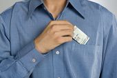 picture of button down shirt  - Mid section view of a man putting money in shirt pocket - JPG