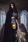 stock photo of cloak  - girl in a black cloak with a lantern on the bridge - JPG